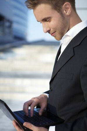 Closeup portrait of a happy young businessman using laptop on street photo