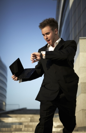 Checking the time. Worried young businessman photo