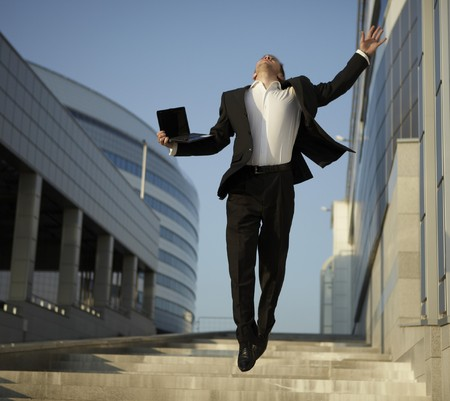Jumping businessman over urban background photo