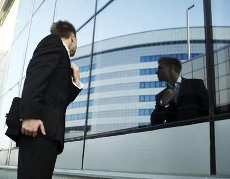 mirar espejo: Hombre de negocios vano comprobando su mira en el espejo