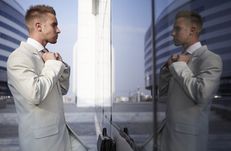 self conceit: Vain business man checking his looks in the mirror