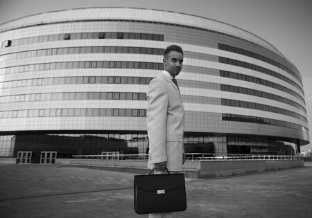 Young businessman portrait against urban background