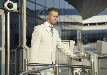 turnstile: young caucasian businessman standing at the security gate Stock Photo