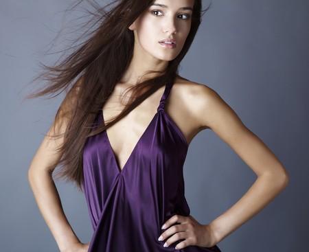 Sexy brunette posing in silk violet dress. photo