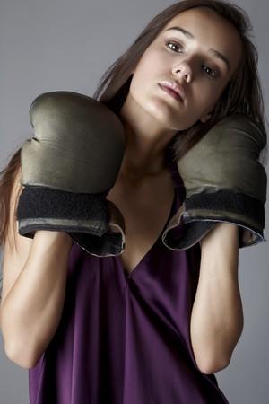 morena sexy: Sexy Morena en los guantes de boxeo posando vestida de seda de vestido violeta.  Foto de archivo