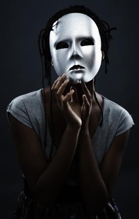 Gloomy Woman in Silber Maske posiert auf einem schwarzen Hintergrund.