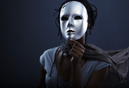 drama mask: gloomy woman in silver mask posing on a black background.