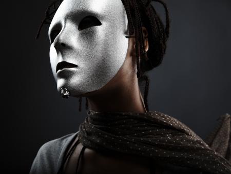 düstere Frau in Silber Maske posiert auf einem schwarzen Hintergrund.