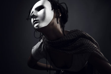 gloomy woman in silver mask posing on a black background. photo