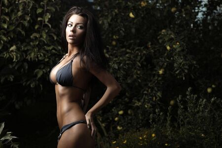 Sexual beauty dressed bikini poses in an autumn garden of apples. Stock Photo - 8039042