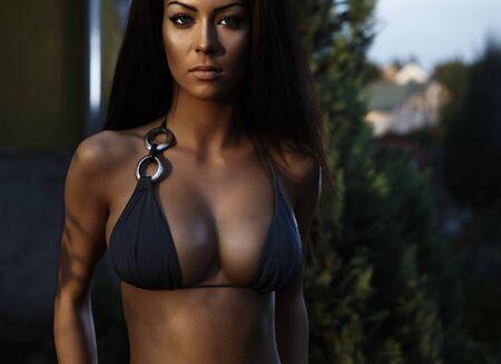 Vêtus de beauté sexuelle dans des poses de bikini près de bâtiment