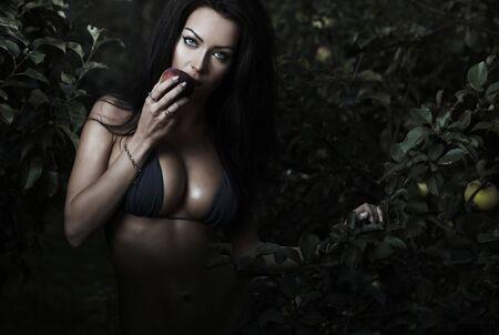 Beauté sexuelle habillé bikini poses dans un jardin automne de pommes.