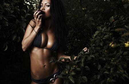 Beauté sexuelle habillée bikini poses dans un jardin automne de pommes.