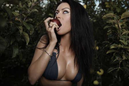 deseo sexual: Poses de bikini de belleza sexual vestida en un jard�n de oto�o de manzanas.