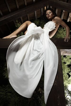 suntanned: Attractive suntanned girl in white dress poses on a wooden beam.