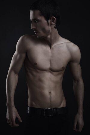 chest hair: Beautiful athletic caucasian man on dark background Stock Photo