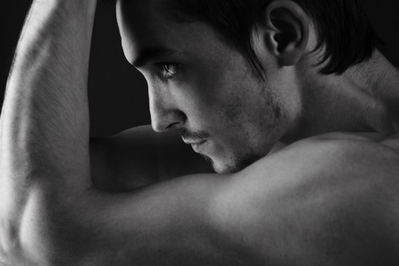 muscular male: Beautiful athletic caucasian man on dark background Stock Photo