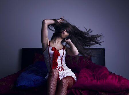 bedsheets: Ragazza seduta sul letto agitando capelli lunghi Archivio Fotografico