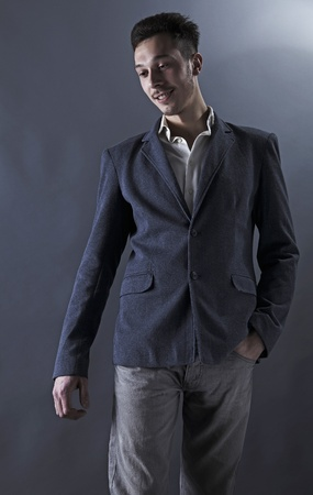 Young attractive man in suit on gray background photo