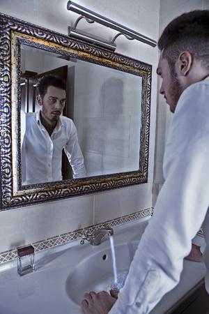 mirada triste: Hombre echa un vistazo a s� mismo en el espejo.