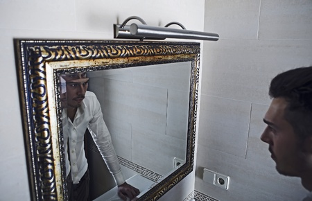 look in mirror: Man takes a look at himself in the mirror.
