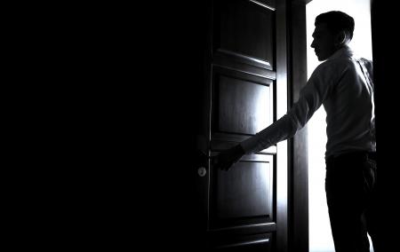 porta aperta: uomo apre la porta di una stanza buia Archivio Fotografico