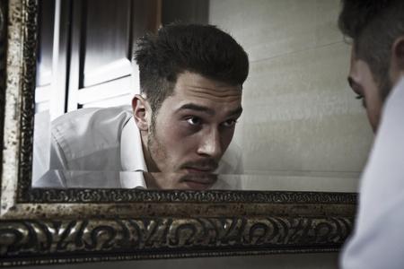 Homme jette un regard sur lui-même dans le miroir.