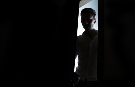 man opens the door to a dark room Stock Photo - 8596628