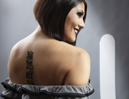 Portrait of a pretty girl with tattoo on her back photo