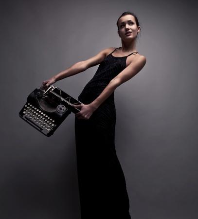 Femme élégante posent avec photo machine à écrire ancienne mode conceptuelle Banque d'images