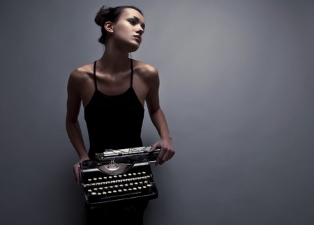 type writer: Elegant woman pose with ancient typewriter  Conceptual fashion photo   Stock Photo