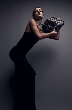 Femme élégante posent avec une photo de machine à écrire ancienne mode conceptuel