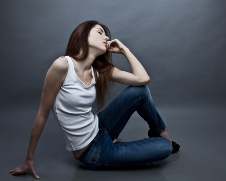 Young attractive woman siting on the studio floor Stock Photo - 12962160