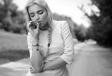 woman with cigarette in summer scenery