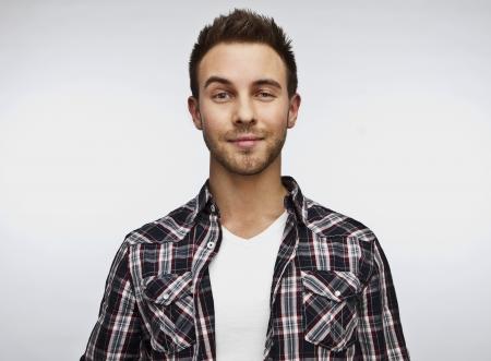 man close up: Attraente uomo bello positivo - vicino ritratto su sfondo bianco grigio