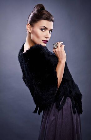 Close-up face portrait of stylish fashionable pretty woman in fur against grey background   photo