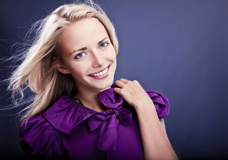 Fashionable blond girl smiling on violet dress   photo