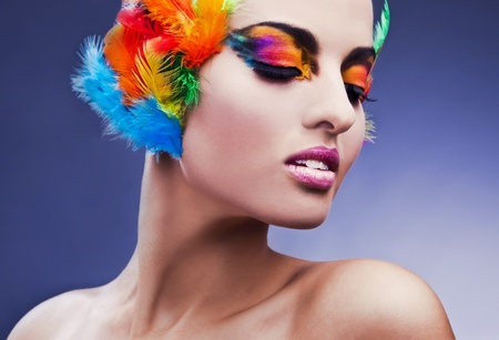 Beautiful young female face with bright fashion multicolored make-up   feathers   Stock Photo