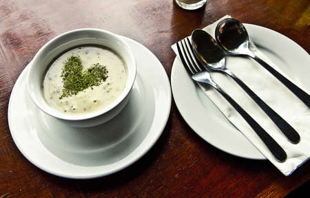 Mushroom soup with parsley in white ceramic bowl photo