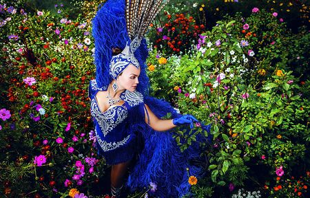 Woman in expensive exotic carnival suit pose in meadow of flowers Stock Photo - 15598556