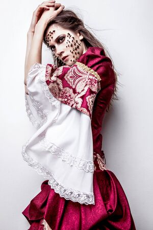 psychologically: Fine art photo of a young lady in medieval dress with thorns of roses on her face