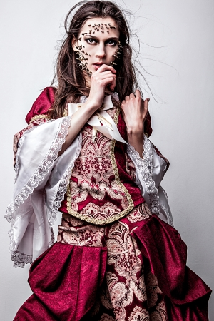psychologically:   a young lady in medieval dress with thorns of roses on her face   Stock Photo