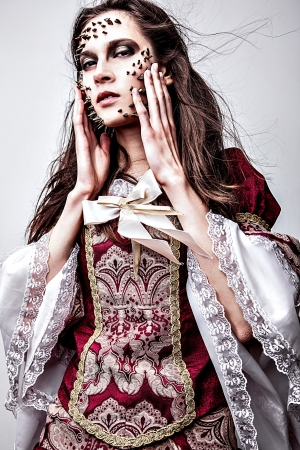 a young lady in medieval dress with thorns of roses on her face   photo