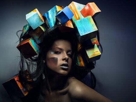 Fashion close-up portrait of beautiful young girl with cubes on head  Conceptual photo   photo
