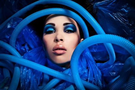 Futuristic beautiful young female face with blue fashion make-up   photo