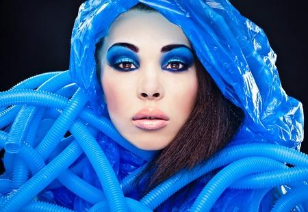 Futuristic beautiful young female face with blue fashion make-up   photo