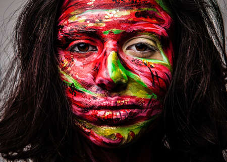 Close-up portrait of an artistic woman painted with red   green color  Part of face photo   photo