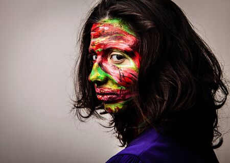 drow: Close-up portrait of an artistic woman painted with red   green color  Part of face photo   Stock Photo