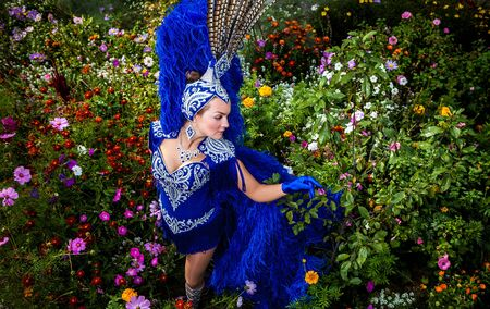 mistic: Woman in expensive exotic carnival suit pose in meadow of flowers