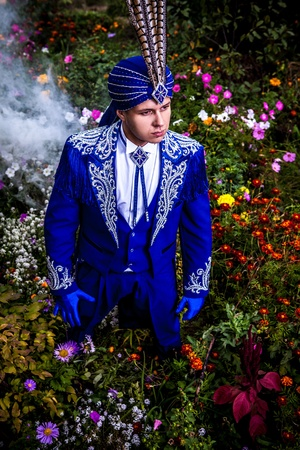 Man in expensive dark blue suit of illusionist pose on flower meadow Stock Photo - 15588381